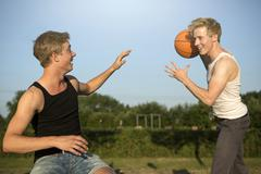 germany, two young man meeting up to play basketball - stock photo