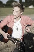 germany, young man sitting in park holding guitar - stock photo