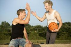 germany, two young men meeting up to play basketball - stock photo