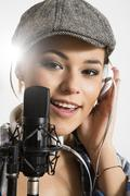 portrait of young woman singing in microphone, smiling - stock photo