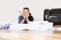 portrait of young woman planning her first apartment, smiling - stock photo