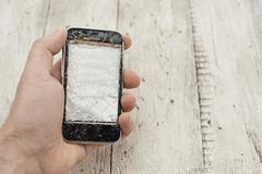mid adult man holding broken cellphone, close up - stock photo
