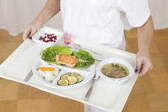 germany, young woman holding patient tray with main meal, close up - stock photo