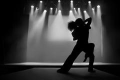 couple in silhouette dancing on a stage - stock photo