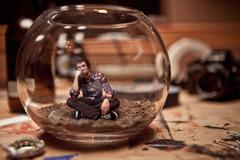 Unhappy miniature man trapped inside a fishbowl. Stock Photos