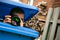 paparazzi hiding in a blue garbage bin - stock photo