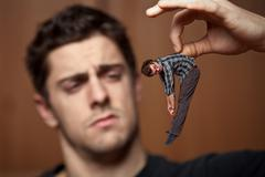 Miniature man got caught by a giant Stock Photos