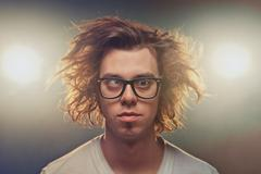 funny squinting man with tousled brown hair in studio - stock photo