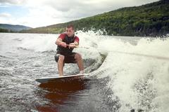 Happy handsome man wakesurfing in a lake Stock Photos