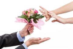 man giving flowers to his wife after argument - stock photo