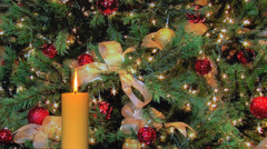 Golden candle with blinking Christmas tree lights Stock Footage