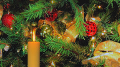 Gold candle with blinking Christmas tree lights Stock Footage
