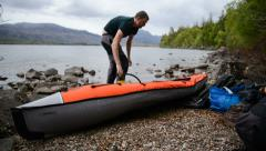 Inflating kayak in scotland Stock Footage