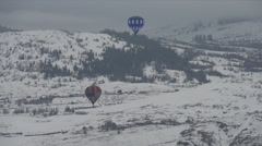 Hot air balloon, flight snow valley, long shot, hills in bg Stock Footage
