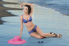 pretty brunette in blue bikini with arm on the head - stock photo