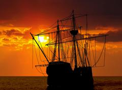 pirate ship during sunset - stock illustration