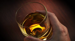 Whisky swirling in a plane glass Stock Footage