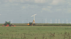 Tracktor green passing by windturbines background Stock Footage