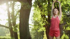Pretty Girl Stops for Stretching during Run in Park. Jib Shot.  4K Stock Footage