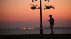 An Kid  Walking On Coastal Street At Sunset Stock Footage