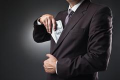 businessman putting money in his pocket on dark - stock photo