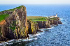 view of neist point lighthouse and rocky ocean coastline, scotland - stock photo