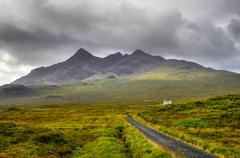 cuillin hills mountains with lonely house and road, scotland - stock photo