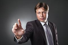 Businessman pressing an imaginary button on bokeh Stock Photos