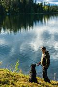 Stock Photo of fisherman and dog