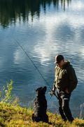 fisherman and dog - stock photo