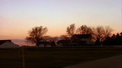 Tracking shot right to left of farmhouses with sunset Stock Footage