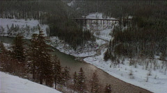 Wide shot train passing over trestle from left to right in snowy mountain - stock footage