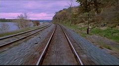 Point of view from train engine running down tracks and water on left Stock Footage
