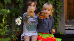 Two girls eating apples, playing dogs toys Stock Footage