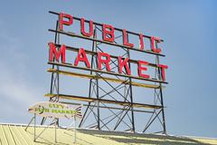 Neon public market sign against sky Stock Photos