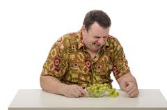 Stock Photo of Middle aged guy eating sour grapes