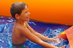 Smiling boy in the water near waterslide. Stock Photos