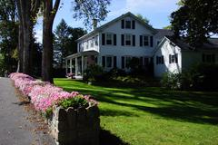 Colorful flowers and classic new england home Stock Photos