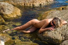 beautiful woman lying on a rock - stock photo