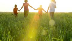 happy young family with children  running around the field - stock footage