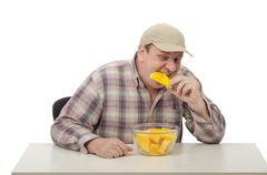 Stock Photo of Countryman tasting cut yellow watermelon