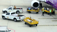 Stock Video Footage of Baggage Handlers Offloading Luggage From Plane