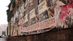 Business man walks past torn old posters in Rome Stock Footage
