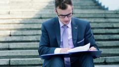 Young businessman reading documents on stairs HD Stock Footage