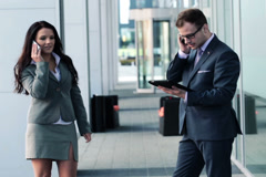 Young business people with cellphone and tablet by office building NTSC Stock Footage