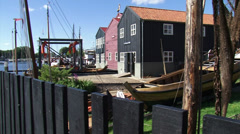 Pan traditional shipyard with restored wooden boat , a botter, in foreground Stock Footage