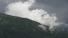 Time-lapse, clouds forming over forested ridgeline Stock Footage