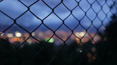 CITY LIGHTS BEHIND WIRE FENCE - NIGHT Stock Footage