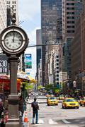 Urban city life with taxis passing by 5th avenue and a big street clock, NY Stock Photos