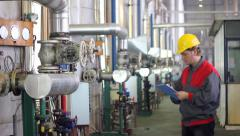 Industrial worker writes on clipboard Stock Footage
